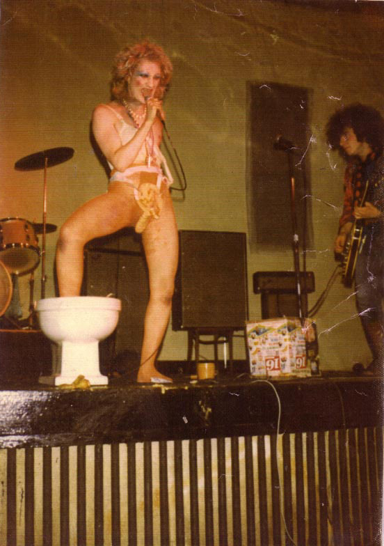 Wayne on stage with foot in a toilet